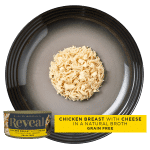 Isolated aerial close up of Reveal chicken cat food with cheese on a plate